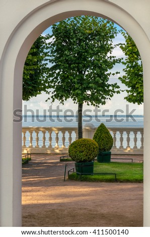 View through stone arch to the terrace and ornamental trees on the sea background - stock photo