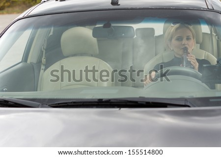 View through the front windscreen of a female driver drinking alcohol from a bottle in the car while driving along the road - stock photo