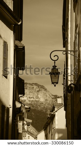 View through the narrow medieval street on the mountains at background during sunset (Annecy, France). A game of  contrasting light and shadow. Aged photo. Sepia.