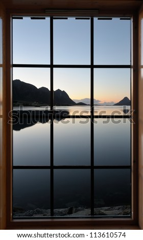 View through the window at the sunrise over the fjord - stock photo