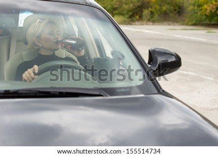 View through the windscreen of a blond woman drinking alcohol directly from a bottle while driving a car - stock photo