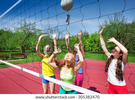 View through volleyball net of playing girls trying to catch the ball on the playground during summer sunny day - stock photo
