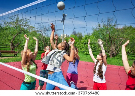 View through volleyball net of playing teens - stock photo