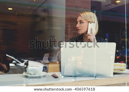 View through window of a young businesswoman is calling via mobile phone to her partner which she waiting in coffee shop. Hipster girl is phoning via cell phone during work on portable laptop computer - stock photo