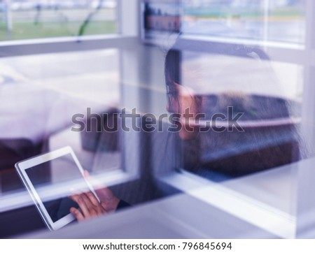 View through window of businesswoman looking at  tablet
