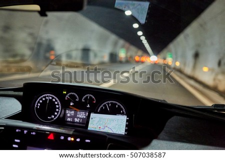 View through windscreen of car moving by road in tunnel.