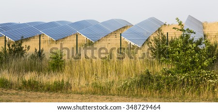 View to a large solar panel park behind a fence in green landscape. - stock photo