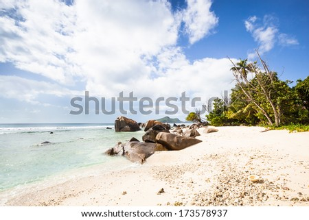 view to a lonesome white beach with tropical palms, granite rocks and trees, a turquoise sea and a cloudy sky, Mahe, Seychelles, Africa