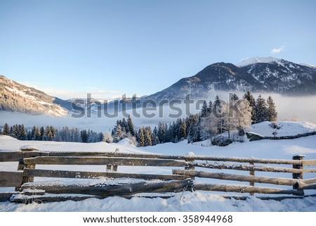 View to a winter landscape with wooden fence, Gasteinertal valley near Bad Gastein, Pongau Alps - Salzburg Austria Europe - stock photo