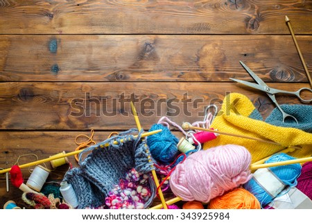 view to a wooden table with lots of balls of wool, knitting needles and other tools.  Place for text - stock photo