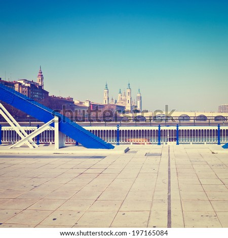 View to Cathedral through Elements of the Metal Bridge in Zaragoza, Retro Effect - stock photo