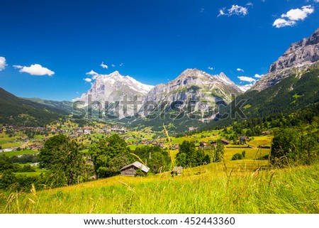 View to famous Grindelwald valley, green forest, Alps chalets and Swiss Alps (Schreckhorn, Berglistock and Wetterhorn) in the background, Berner Oberland, Switzerland, Europe. - stock photo