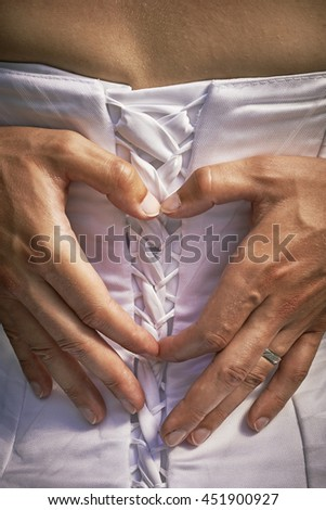 View to forming of the groom hands on the backs of the bride heart symbol