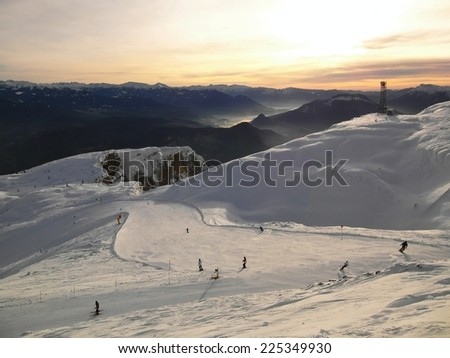 View to free terrain at snowy slope in Alps ski resort. Dark green trees sticking out from frost snow. - stock photo