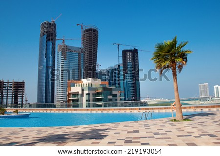 View to new city district of Abu Dhabi, UAE. Swimming pool at foreground.