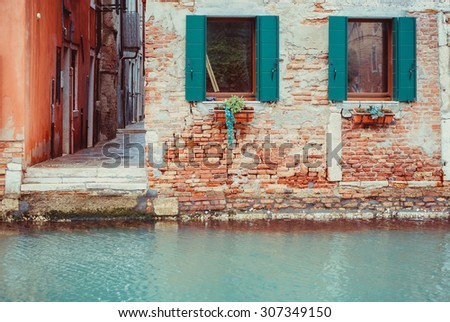 View to old building brick facade from the channel in Venice, Italy. The facade with two emerald green wooden windows.  - stock photo