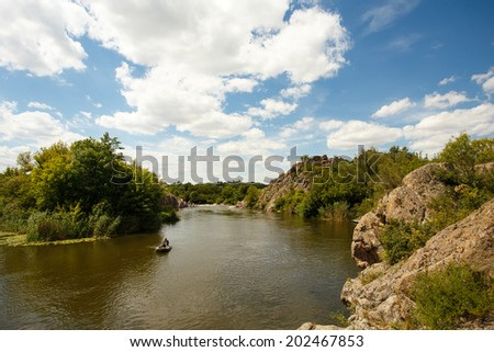 view to river with reflections and blue cloudy sky