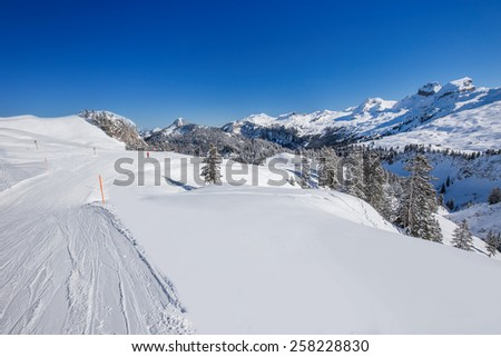 View to Skiers on the ski slopes and Swiss Alps covered by fresh new snow seen from Hoch-Ybrig ski resort, Central Switzerland - stock photo