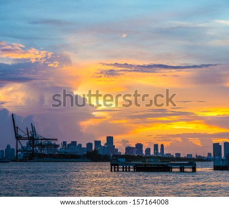 view to skyline of Miami with docks in foreground at sunset - stock photo