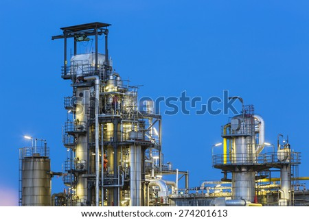 View to the distillation towers of a chemical plant and refinery with night blue sky and illumination.