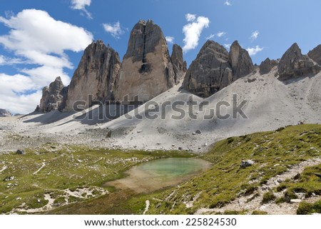 View to the famous Tre Cime di Lavaredo (German: Drei Zinnen). The meadow in foreground is seen a typical alpine pasture. The Tre Cime are part of the National Park Sexten Dolomites.  - stock photo