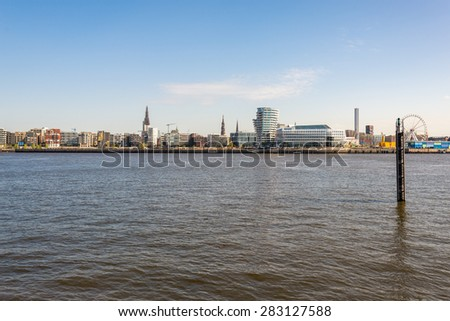 View to the HafenCity from the harbor side Hamburg. The HafenCity is a brand-new district in the former free port of Hamburg and has plenty of new modern office buildings and residential blocks - stock photo
