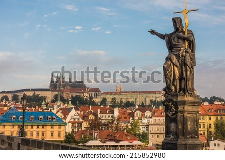View to the lesser town and the Prague Castle from Charles Bridge having a statue of John the Baptist in the foreground - stock photo