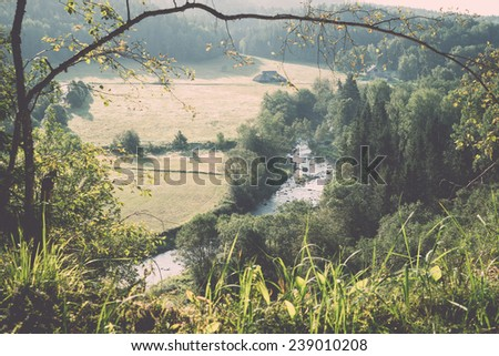 view to the mountain river in summer surrounded by forest and sandstone cliffs - vintage retro film look - stock photo