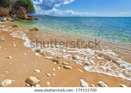 View to tide wave over pebbles and rocks on the sand under transparent water at Ionian sea floor under bright sunlight near Ipsos, Corfu, Greece - stock photo