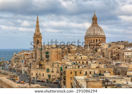 View to Valetta city buildings including Our Lady of Mount Carmel and St Pauls Pro-Cathedral under clouds, Malta  - stock photo