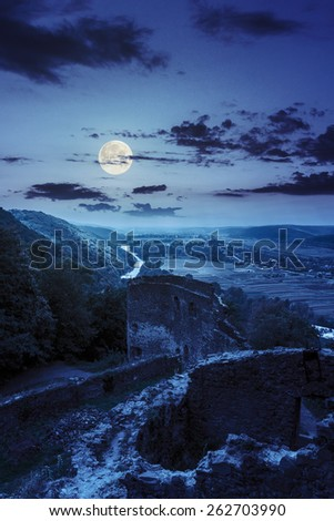 view to village in vally from stone wall of an old ruined castle in the mountains at night in full moon light - stock photo