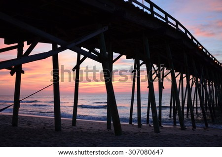 View under the pier. Sunrise at Kure Beach North Carolina on a warm summer morning.
