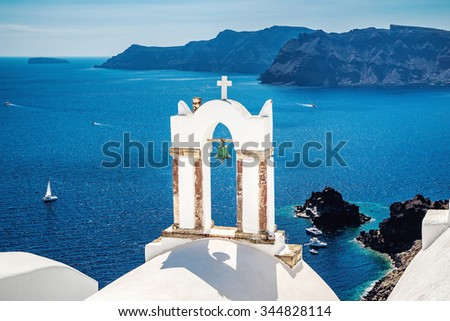 View with bell tower and white orthodox church and blue sea in the village of Oia, Santorini island, Greece.  - stock photo