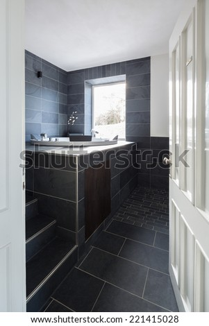 Viewed through a white painted wooden door into a modern tiled bathroom interior with charcoal grey wall and floor tiles and a built in vanity - stock photo