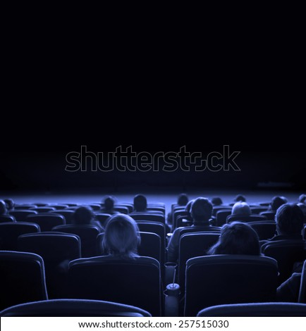viewers watch motion picture at movie theatre, long exposure, blue toning - stock photo