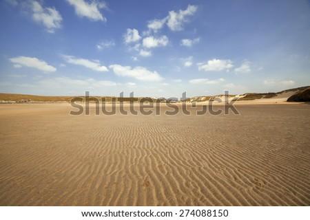 Views looking across an empty textured Cornish beach towards the sand dunes. - stock photo