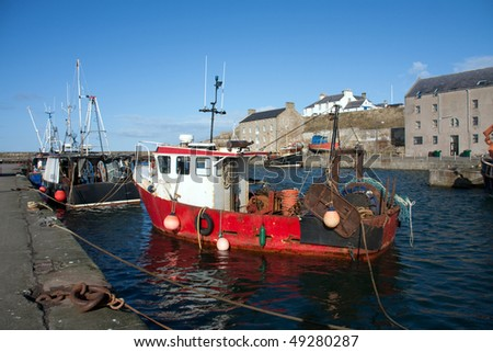 Views of Burghead harbour with the fishing fleet in port Scotland UK - stock photo