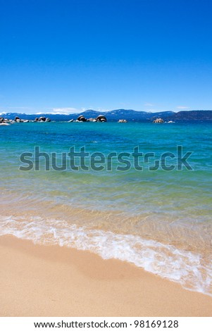 Views of Lake Tahoe in California with crystal clear water, snow on the ground, and mountains in the background.
