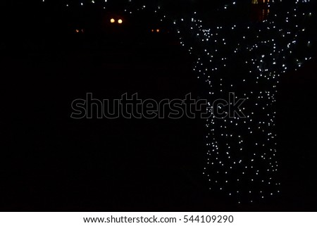 Views of white garlands on a dark background in night city