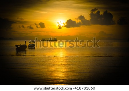 Vignette filter of Silhouette traditional long boat during sunset or sunrise at Andaman sea, Thailand. Concept for tropical beach, vacation, nature, relax, morning, fresh, summer, background - stock photo