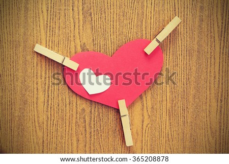 Vignette Style, Series of Valentines Card. Red heart paper cut with clothes pin on wooden background. Image of Valentines day. Photoshop Vintage Effect. - stock photo