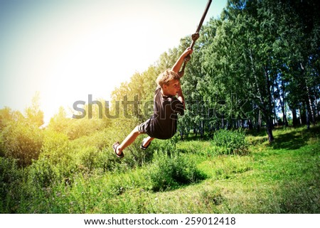 Vignetting Photo of Kid Bungee jumping in the Summer Forest - stock photo