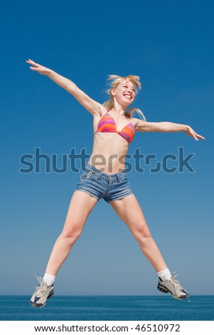 Vigorous blond woman in shorts and top of swimsuit is jumping outdoors