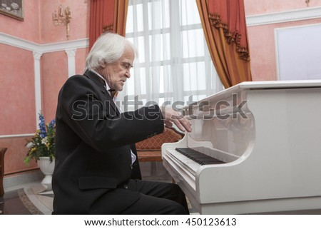 Vigorous charming aging musician playing the white piano
