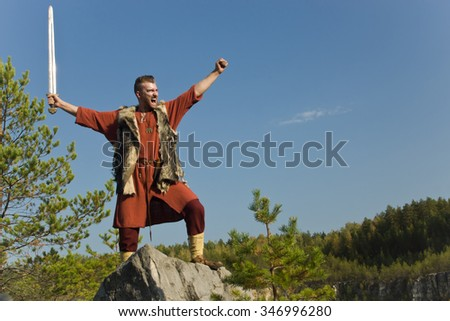 Viking attacking with a sword in the mountains  - stock photo