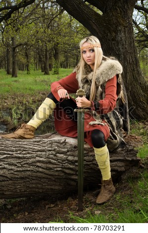 Viking girl warrior with sword in a wood - stock photo
