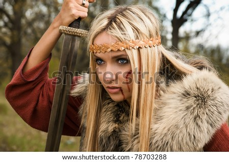 Viking girl with sword in a fog wood - stock photo