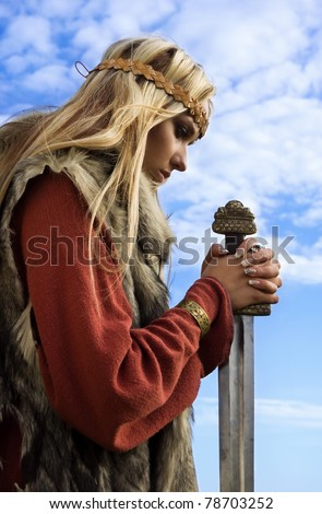 Viking girl with sword on a blue sky background - stock photo