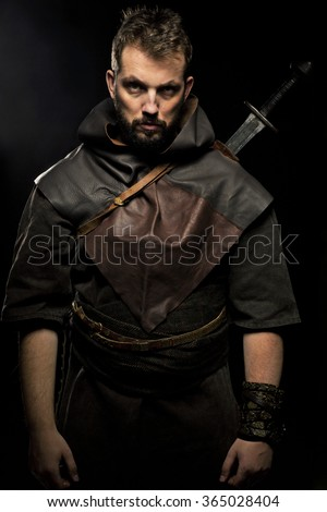 Viking warrior with sword over black background with angry look - stock photo