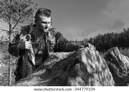 Viking with a sword on a cliff in the mountains - stock photo